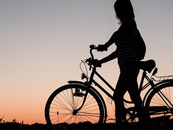 woman on bike with sunset