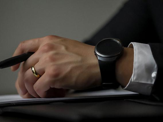 mans hand holding pen