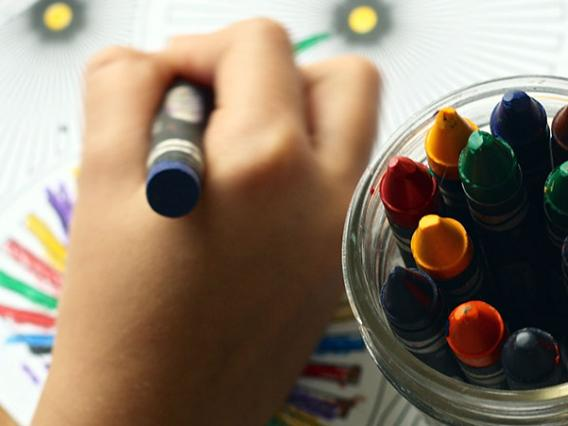 child's hand with crayons