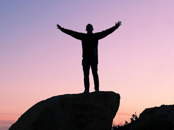 man standing on rock triumphantly